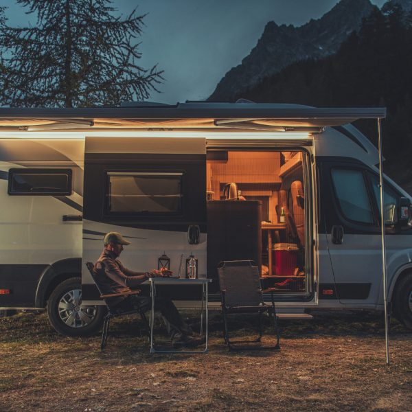 Caucasian Men in His 40s Working Online While on Vacation in Mountain Region. Remote Work on Laptop While Camping in a Wild. Camper Van as Mobile Office Theme.